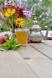 Cup of tea with colorful bouquet of flowers on a table in garden. Cup of mint tea with colorful bouquet of flowers on a table in garden royalty free stock images