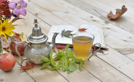 Cup of mint tea with flowers and mint leaf. On a table royalty free stock image
