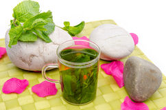Cup of mint tea, fresh mint, pebbles and pink petals on a green Royalty Free Stock Photo