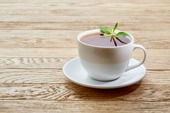 Cup of mint tea and green leaves on light table Stock Images