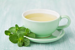 Cup of mint tea and green leaves on light table Royalty Free Stock Images