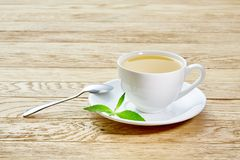 Cup of mint tea and green leaves on light table Stock Image