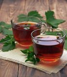 Cup of mint tea and leaves of mint on the table. Herb tea. Healing herbs. stock images