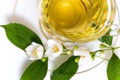Cup mit Blättern des grünen Tees und des Grüns Stockfotos