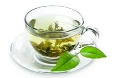 Cup mit Blättern des grünen Tees und des Grüns. Stockfotos