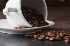 Cup mit Kaffeebohnen auf dunklem Hintergrund Lizenzfreie Stockfotos