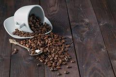 Cup mit Kaffeebohnen auf dunklem Hintergrund Lizenzfreies Stockfoto