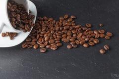 Cup mit Kaffeebohnen auf dunklem Hintergrund Stockfotos