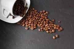 Cup mit Kaffeebohnen auf dunklem Hintergrund Stockfotografie