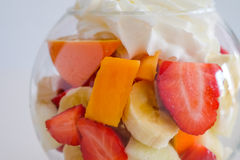 Cup of mixed fruits with cream up royalty free stock photos