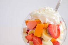 Cup of mixed fruits with cream up stock image
