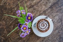 Cup of mocha coffee with fake flower. On old wooden table in coffee shop Royalty Free Stock Photo