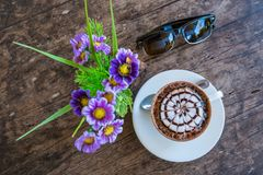 Cup of mocha coffee with fake flower and sun glass. On old wooden table in coffee shop Stock Photo