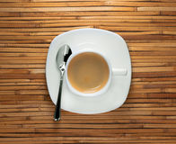 Cup of morning black espresso coffee on saucer with metal spoon on reed background Royalty Free Stock Photos