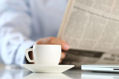 Cup of morning coffee with businessman on background. Cup of morning coffee on worktable with business analyst hold in hands and read newspaper on background stock photography