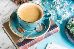 A cup of morning coffee. A cup of hot and refreshing morning coffee. Cappuccino in blue craft cup with spoon. Toned, selective focus on coffee surface Royalty Free Stock Image