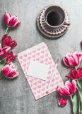 Cup of morning coffee with pink tulips and blank paper card with hearts on table background, top view. Holidays breakfast. Flat lay style. Greeting card mock Royalty Free Stock Image