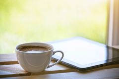 Cup of coffee with tablet computer stock photos