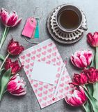 Cup of morning coffee with tulips flowers and blank paper card mock up with hearts, top view. Holidays breakfast. Flat lay style. Greeting card concept Royalty Free Stock Photography