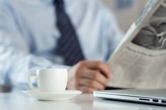 Cup of morning coffee on worktable with businessman reading news Stock Photography