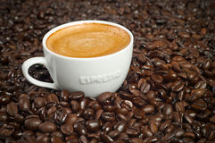 Cup of Morning Espresso in Roasted Coffee Beans. Cup of Morning Espresso in Dark Roasted Coffee Beans background steaming with frothy crema on top Stock Photos
