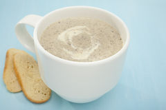 Mug of Mushroom Soup on Blue Background Royalty Free Stock Photography