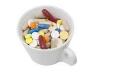 Cup of multicolored tablets and capsules Stock Image
