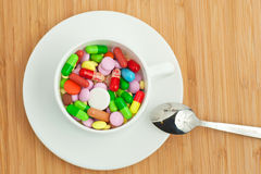 Cup with multicolored tablets and capsules Stock Photography