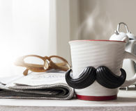 Cup with mustache on wooden table Royalty Free Stock Photos