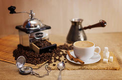 A Cup of natural coffee, coffee beans, Arabica, cinnamon stick. Aromatic coffee, natural grain, Arabica. Shows a hot Cup of coffee, coffee beans, hand grinder stock photo