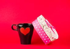 Cup near gift on red background, concept of valentine day Royalty Free Stock Photos