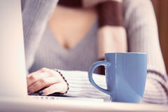 Cup near a woman with notebook computer Royalty Free Stock Images