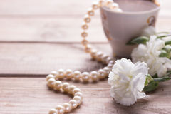 Cup necklace and white flowers Stock Photos