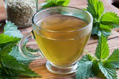 A cup of nettle tea on a wooden table stock image