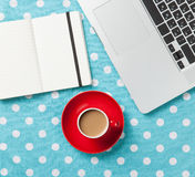 Cup and notebook near laptop comuter Stock Image