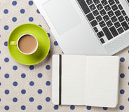 Cup and notebook near laptop comuter Stock Photos