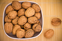 Cup of nuts on bamboo table cloth Stock Photos