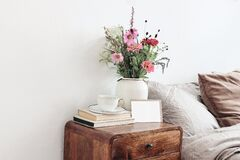 Free Cup Of Coffee And Books On Retro Wooden Bedside Table. Blank Greeting Card Mockup. White Ceramic Vase. Buquet Of Cosmos Royalty Free Stock Photo - 217684995