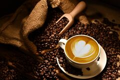 Free Cup Of Coffee Latte With Heart Shape And Coffee Beans On Old Wooden Background Stock Photos - 169308633
