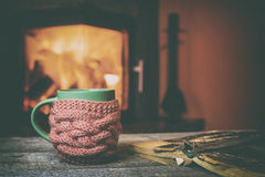 Cup, old book, glasses on vintage wood near fireplace royalty free stock photo