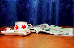 Cup and opened magazine. Cup of coffee with small cup of cream and spoon on saucer and opened magazine Stock Photography