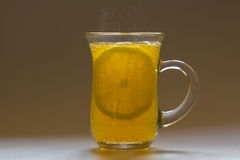 Cup with orange drink and lemon Royalty Free Stock Photography