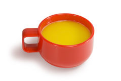 Cup with orange juice. Orange juice in a red cup. On a white background Stock Images