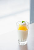 Cup of orange panna cotta on the table Royalty Free Stock Image