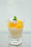 Cup of orange panna cotta on the table Royalty Free Stock Photo