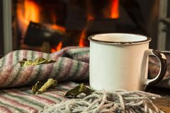 A cup over fireplace on wooden table. Stock Photo
