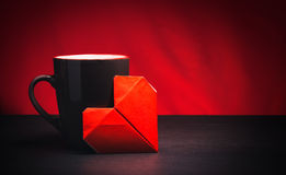 Cup and paper heart. On a dark wooden table and red background Royalty Free Stock Photos
