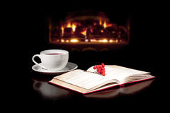 Cup of peace. Cap of tea and book on the table top with fireplace in the background stock photos