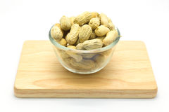 Cup of peanuts on wooden board on white Royalty Free Stock Image