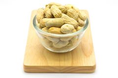Cup of peanuts on wooden board Royalty Free Stock Photos